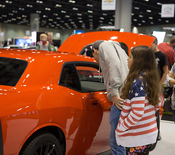 Father and daughter look at orange car on convention center floor
