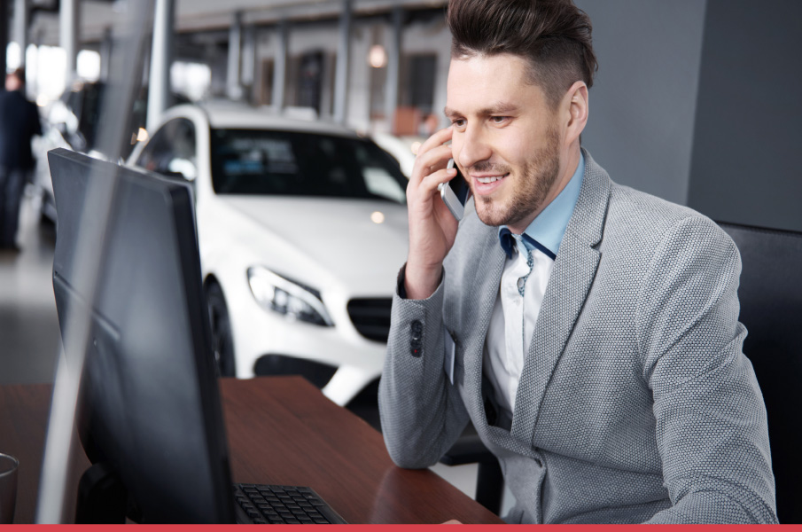 Car salesman talking on the phone and looking at his computer on sales floor
