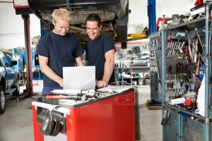 Auto Techs working on laptop in auto repair shop, Over-the-air (OTA) fix